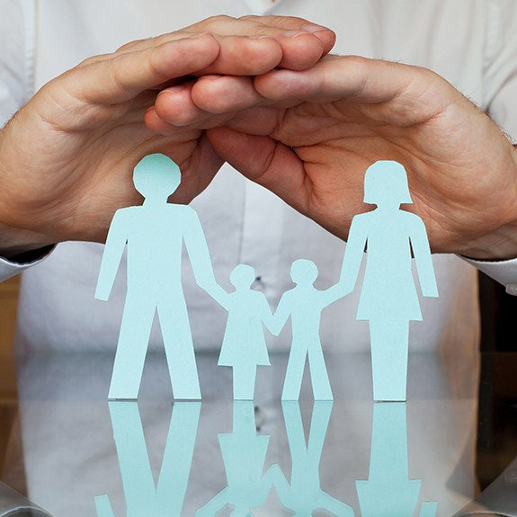 Hands covering a paper cut out family