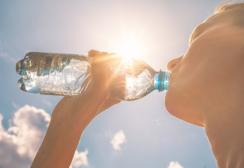 woman drinking water outside during summer